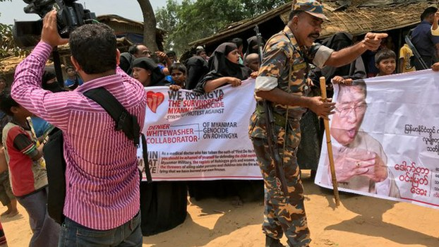 A Bangladeshi security official blocks Rohingya refugees from demonstrating against the visit of Myanmar Social Welfare Minister Win Myat Aye to the Kutupalong camp, April 11, 2018.