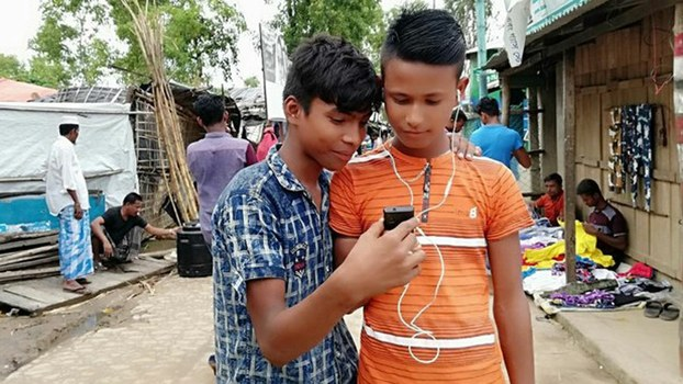 Rohingya teens use a cellphone to access the internet at a refugee camp in Bangladesh's Cox's Bazar district, Aug. 3, 2019.