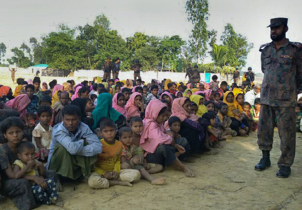 Bangladeshi border police in Teknaf watch over Rohingya Muslims who were detained after trying to cross into Bangladesh from Myanmar, Dec. 25, 2016.