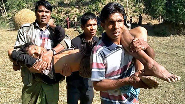 Rohingya men carry a child injured in an explosion on a hill near Htikehtoopauk village, Buthidaung township, in Myanmar's northern Rakhine state, Jan. 7, 2020.