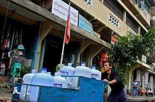 A delivery man walks past an Election Commission office in downtown Rangoon (Yangon) on August 13, 2010.