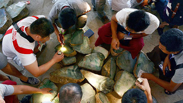 Myanmar gem merchants inspect jade stone on sale in Naypyidaw, Nov. 20, 2016.
