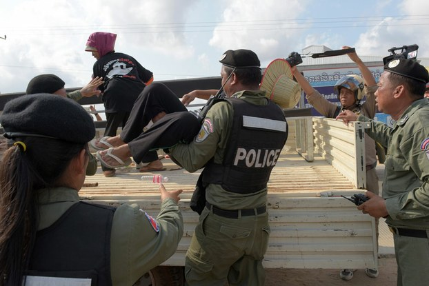 A Cambodian policeman loads a protester into the back of a police truck during a demonstration in Phnom Penh demanding the release of detained rights defenders, May 9, 2016.