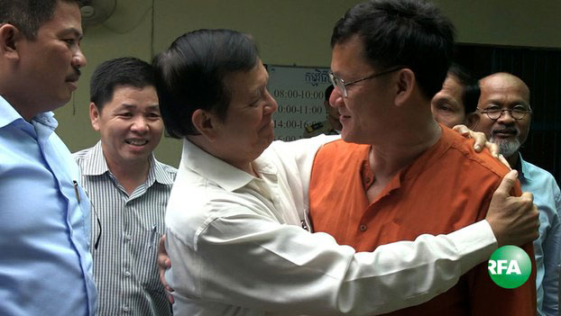 Cambodia National Rescue Party leader Kem Sokha (L) embraces National Election Committee official Ny Chakrya at the General Department of Prisons in Phnom Penh, Dec. 13, 2016.