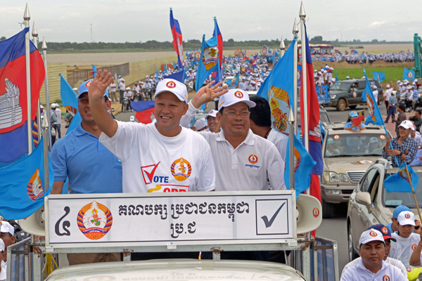 Hun Many(C), Prime Minister Hun Sen's youngest son and a lawmaker from the ruling Cambodian People's Party, waves to supporters during the general election campaign in Phnom Penh, July 21, 2013.