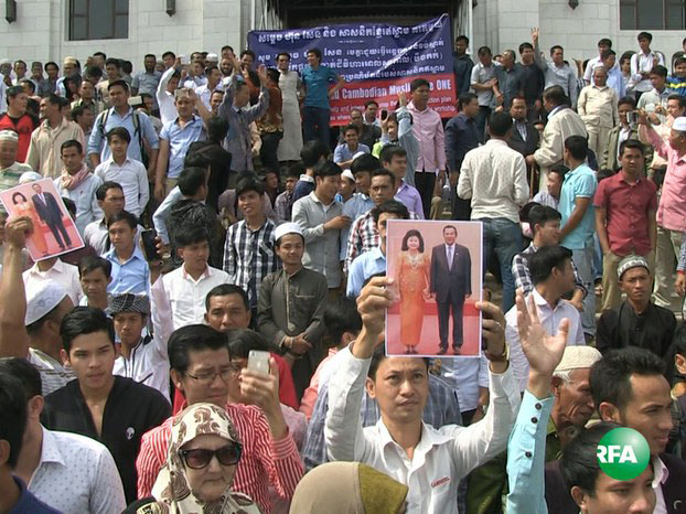 Cham Muslims hold up a photo of Cambodia's first couple as they protest a road project that could divide the property of the Al-Serkal Mosque in Phnom Penh, Dec. 30, 2016.