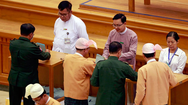 Lawmakers from the Myanmar military and the National League for Democracy party cast votes on bills to amend the 2008 constitution at the national parliament in Naypyidaw, March 10, 2020.