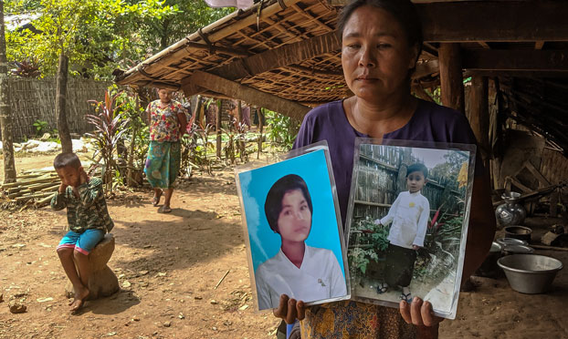 A Myanmar woman holds photos of her children, killed by mortar shells amid armed conflict, in Pan Myaung Village, Minbya township, northern Rakhine state, Oct. 26, 2019.