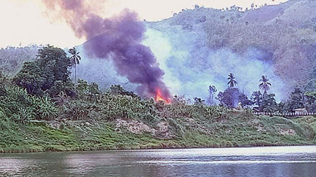 A fire burns homes in lower Meelatwa village, Paletwa township, in western Myanmar's Chin state, May 26, 2020.