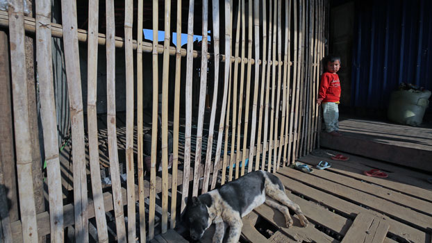 A boy stands at his wooden house in a village in western Myanmar's Chin state, March 3, 2020.