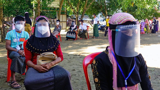 Voters wearing face shields and face masks to prevent the spread of the coronavirus wait in line to cast ballots at a polling station in western Myanmar's Rakhine state, Nov. 8, 2020.