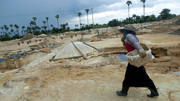 A Myanmar worker carries a basket in a copper mining waste dump area in Monywa, northwestern Myanmar's Sagaing region, in a file photo. Villagers whose lands were grabbed under a former military junta in the copper-rich region use discarded soil from nearby mines, mixed with old aluminum cans, water, and acid, to retrieve copper from the waste.