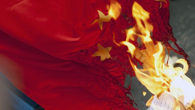 Myanmar activists burn a Chinese flag during a protest against Chinese copper mine company Wanbao in front of the Chinese Embassy in Yangon in a file photo. Wanbao runs the Letpadaung copper mine project in Sagaing region as part of a joint venture with a major Myanmar military conglomerate.