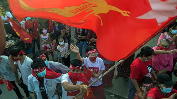 Supporters of Myanmar's National League for Democracy, wearing face masks to protect themselves from contracting the COVID-19 virus, celebrate in Yangon, Nov. 10, 2020, following the party's victory in general elections two days earlier.