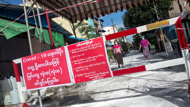 People walk towards a barrier blocking access to minor roads with a sign urging residents to stay at home due to a surge in the number of cases of the coronavirus in Myanmar's commercial city Yangon, Sept. 11, 2020.