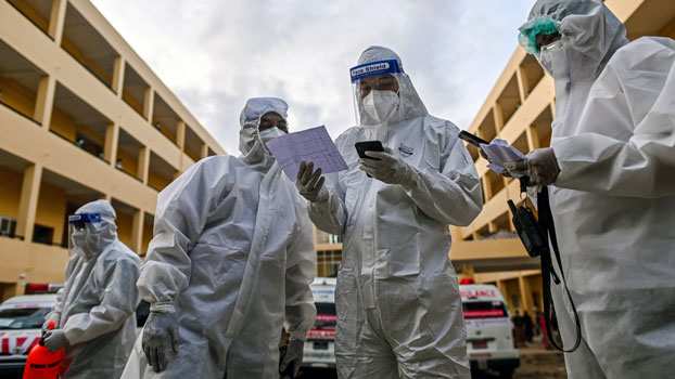 Volunteers wearing personal protective equipment check a list of individuals suspected of having the COVID-19 virus at a quarantine center in Myanmar's commercial city Yangon, Oct. 1, 2020.