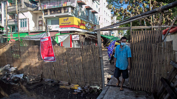 A man walks through a barrier blocking access to minor roads with a sign urging residents to stay at home in Myanmar's commercial hub Yangon, Sept. 11, 2020.