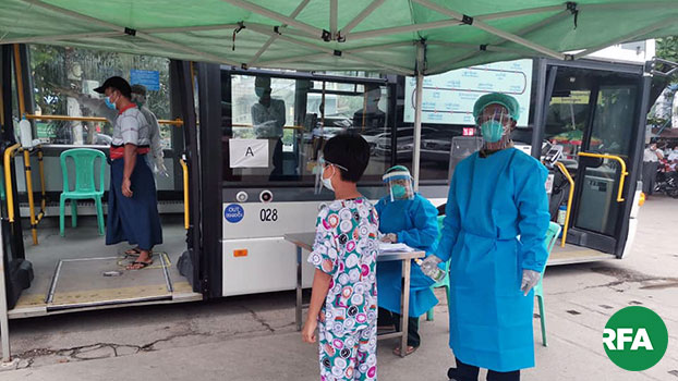 Locals wait to receive medical checkups for signs of the COVID-19 virus at a mobile health clinic on a bus in Thingangyun township, Yangon, Myanmar, Sept. 8, 2020.