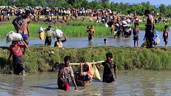 Rohingya refugees carry a woman over a canal after crossing the Naf River as they flee violence in western Myanmar's Rakhine state to reach the Palong Khali campsites near Ukhia in southeastern Bangladesh's Cox's Bazar district, Oct. 16, 2017.