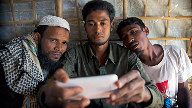 Rohingya Muslim refugee Mohammad Karim (C) shows a mobile video of the Gu Dar Pyin village massacre to other Muslims in the Kutupalong refugee camp, Cox's Bazar district, southeastern Bangladesh, Jan. 14, 2018.