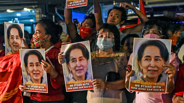 Myanmar supporters of the National League for Democracy hold posters with the image of State Counselor Aung San Suu Kyi as they celebrate in front of the party's headquarters in Yangon, Nov. 9, 2020.