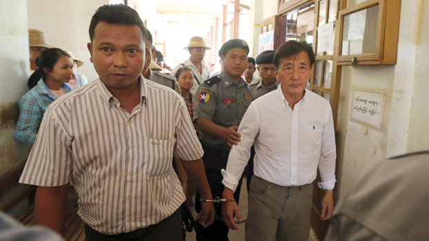 Myanmar national Shein Latt (L) and his boss US national John Fredric Todoroki (R) leave a local court after being arrested for operating a hemp plantation in Ngunzun township, central Myanmar's Mandalay region, May 7, 2019.
