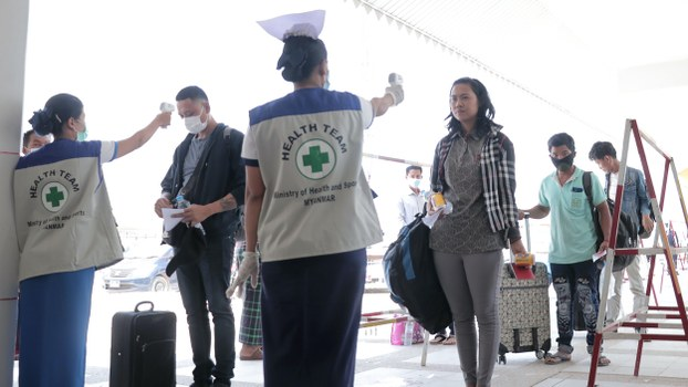 People have their temperatures checked amid concerns over the spread of COVID-19 at a Myanmar immigration post in Myawaddy near the Thai border, March 23, 2020.