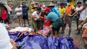 A woman grieves over the dead bodies of miners recovered at a jade mining site following a deadly landslide in Hpakant township, northern Myanmar's Kachin state, July 2, 2020.