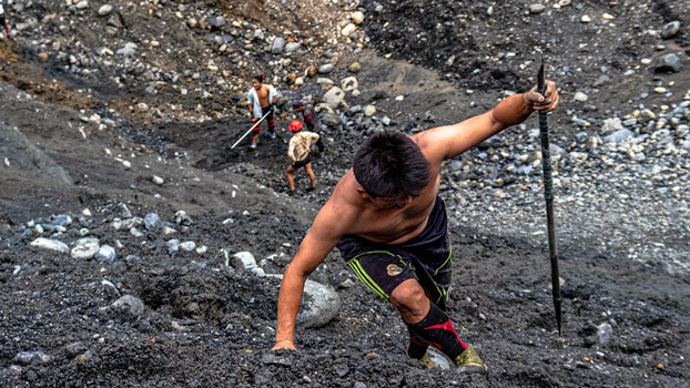 A jade prospector makes his way up a slag heap at a mine near Ma Mon village in Hpakant township, northern Myanmar's Kachin state, July 9, 2020.