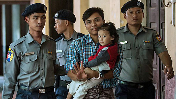Detained Myanmar journalist Kyaw Soe Oo (C) carrying his daughter is escorted by police to his ongoing trial at a court in Yangon, June 12, 2018.