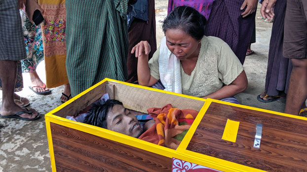 Thein Nu Sein, mother of deceased civilian Zaw Win Hlaing, squats next to her son's coffin following his death from injuries he sustained while in the Myanmar military's custody in Mrauk-U township, western Myanmar's Rakhine state,  July 2, 2019.