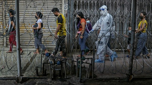 A policeman in protective gear guides migrants to a coronavirus screening booth in the Pudu area of Kuala Lumpur after 15 cases were detected in the neighborhood, May 15, 2020.