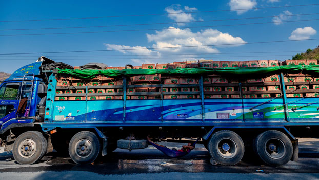 A driver rests under his truck as he waits in line with others to enter China near Muse in Myanmar's northern Shan state, April 20, 2020, after China reduced the number of trucks allowed to enter per day to contain the spread of the coronavirus.