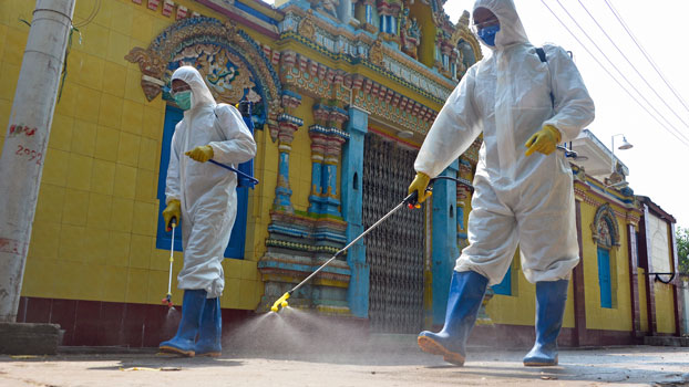 Myanmar military personnel wearing protective clothing disinfect a Hindu temple as a preventive measure to contain the spread of the coronavirus in the capital Naypyidaw, April 1, 2020.