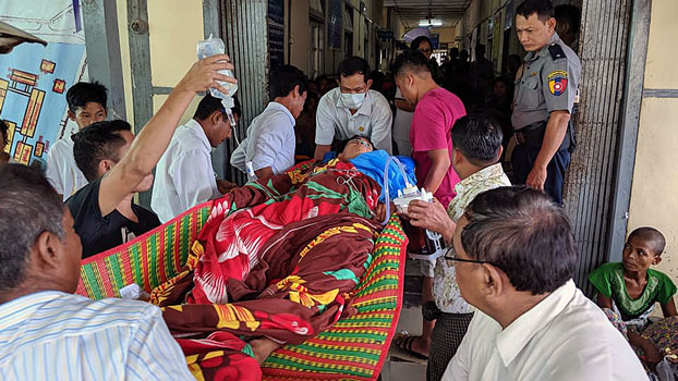 Ye Naing Lin (C), a local employee of the international NGO Plan International, is carried into Sittwe General Hospital in Sittwe, western Myanmar's Rakhine state, to be treated for a gunshot wound, July 29, 2019.