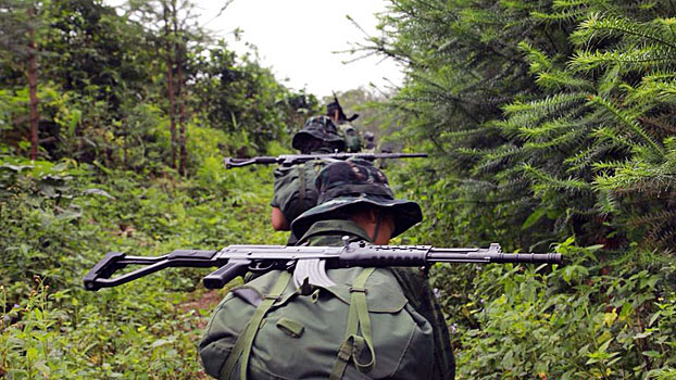 Arakan Army soldiers pass through a wooded area in western Myanmar's Rakhine state in an undated photo.