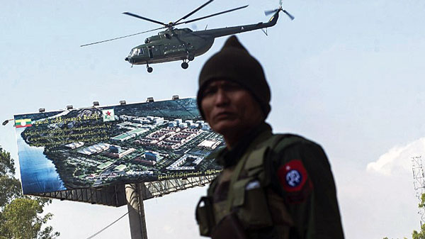 A Myanmar government soldier secures the ground while a military helicopter carrying troops takes off from the town of Muse in eastern Myanmar's Shan state near the border with China, Nov. 25, 2016.
