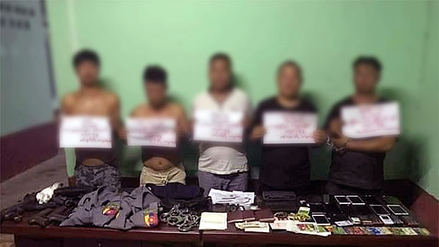 Five Chinese nationals arrested for impersonating police officers stand behind a table with police uniforms and equipment found on them following their apprehension in Laukkai, capital of the Kokang region in Myanmar's northern Shan state, Oct. 15, 2019.