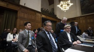 Myanmar's agent, Union Minister Kyaw Tint Swe, center, and members of the delegation take their seats at the International Court in The Hague, Netherlands, Thursday, Jan. 23, 2020.