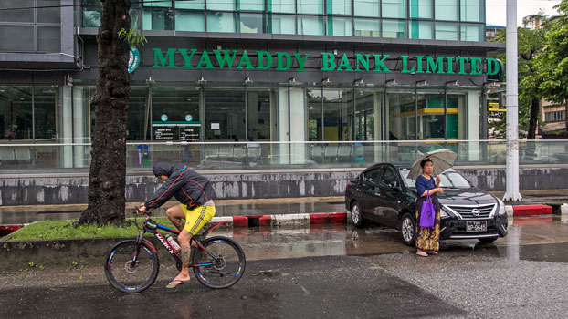 A man on bicycle rides past a Myawaddy Bank branch in Myanmar's commercial capital Yangon, Aug. 5, 2019.