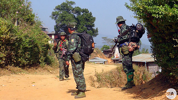 Three soldiers from the Restoration Council of Shan State/Shan State Army-South (RCSS/SSA-S) walk through a village in eastern Myanmar's Shan state in an undated photo.