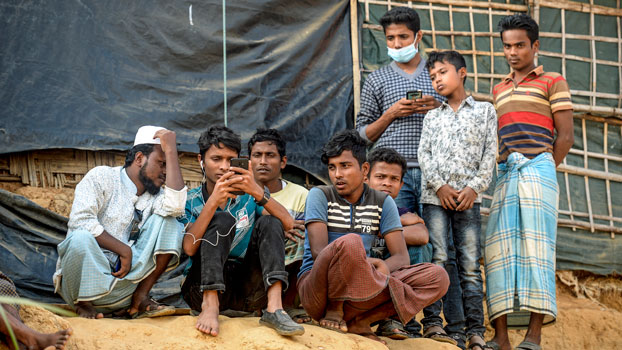 Rohingya refugees watch on a mobile phone a live feed of Myanmar's State Counselor Aung San Suu Kyi's appearance at the UN's International Court of Justice on the second day of the hearing on the Rohingya genocide case, in a refugee camp in Cox's Bazar district, southeastern Bangladesh, Dec. 11, 2019.