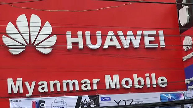 A Huawei sign is seen above a storefront along a busy street in central Myanmar's Mandalay region, May 2019.