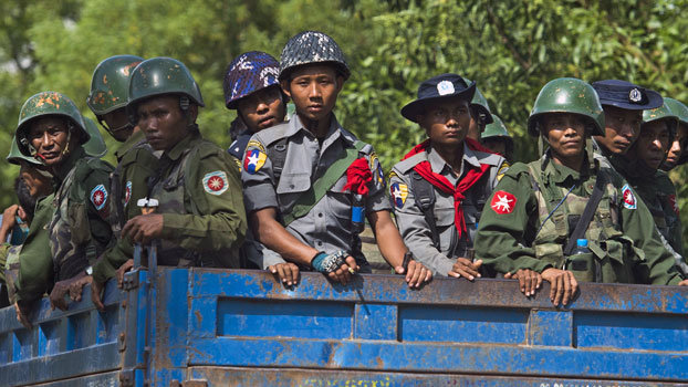Armed military troops and police travel in trucks through Maungdaw township in western Myanmar's Rakhine state, Oct. 14, 2016.