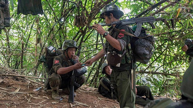 Kachin Independence Army (KIA) soldiers take a cigarette break as they move towards the frontline of fighting with the government army near Laiza in northern Myanmar's Kachin state, Oct. 14, 2016.