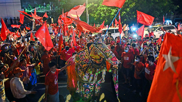 Supporters of Myanmar's National League for Democracy celebrate the party's expected election victory with a traditional elephant dance outside NLD headquarters in Yangon, Nov. 10, 2020.