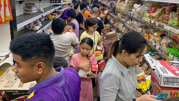 Myanmar citizens grab groceries from shelves in a supermarket in the commercial capital Yangon, after hearing rumors related to the coronavirus, March 12, 2020.