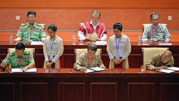 Myanmar military officials, government peace negotiators, and representative of ethnic armed groups sign a document during the closing ceremony of the third session of the Union Peace Conference in Naypyidaw, July 16, 2018.