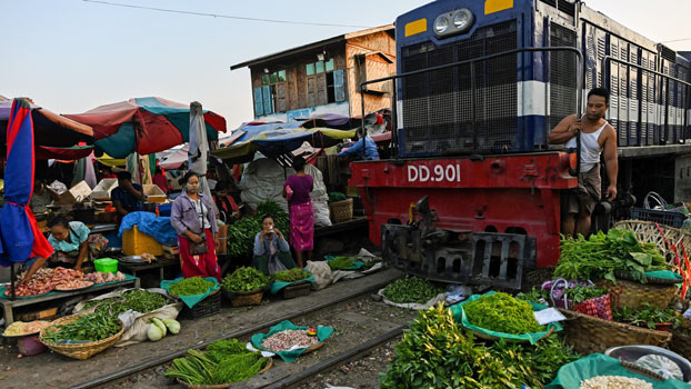 A train waits for vendors to clear the tracks as it makes its way slowly past at a railway bazaar near Tha Ye Zay railway station in Mandalay in central Myanmar, May 19, 2019.