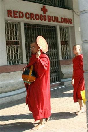Buddhist monks pass a Burmese Red Cross office in an undated photo.